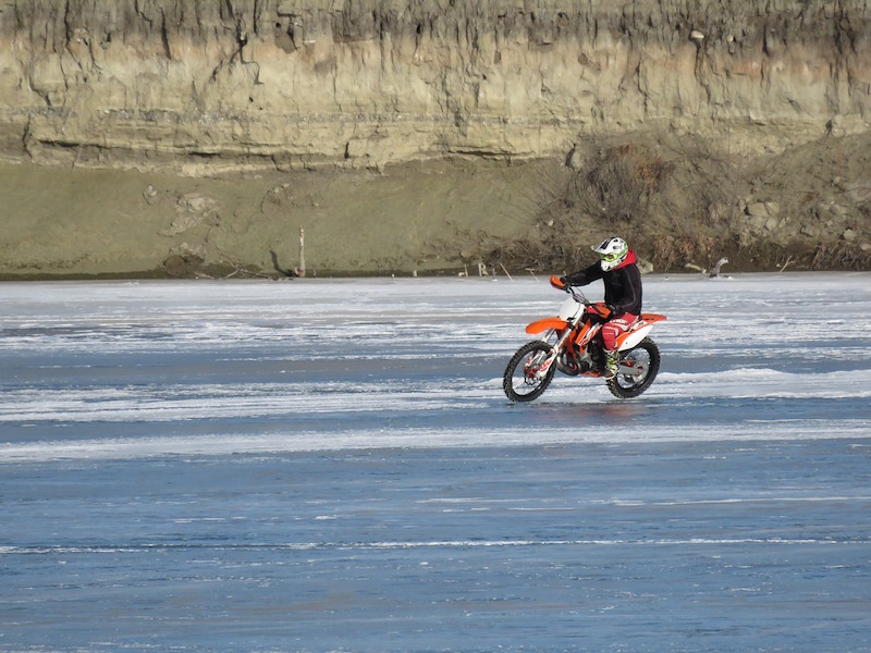 riding a motorcycle on a frozen lake