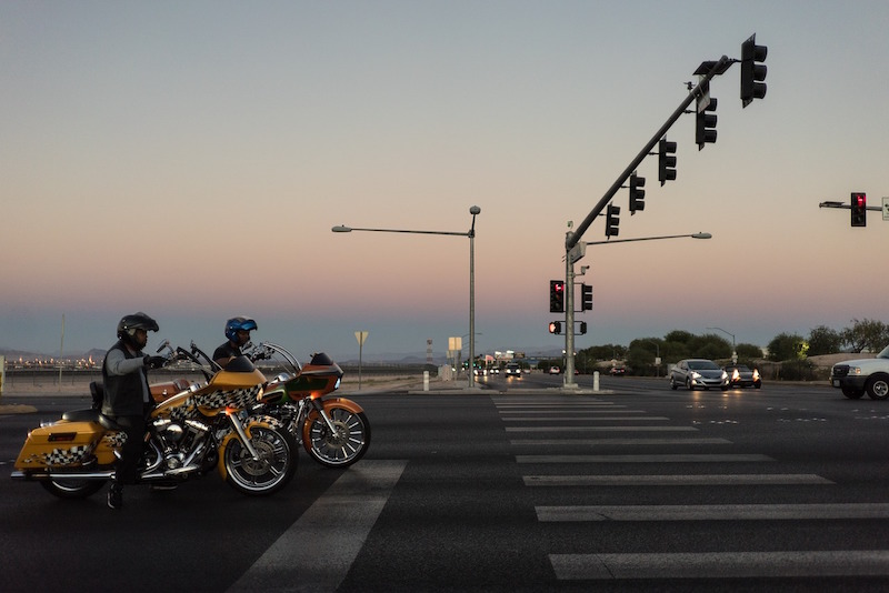Two Harley-Davidson motorcycles waiting at a traffic light